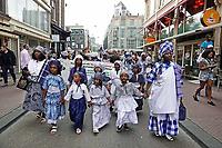 Nederland  Amsterdam - 2018.  Memre Waka optocht door de stad. Op 1 juni wordt in Amsterdam met de herdenkingstocht Memre waka de jaarlijkse Keti koti-maand geopend, die op 1 juli eindigt met de viering van de afschaffing van de slavernij (1 juli 1863). Deze mars wordt georganiseerd door stichting Eer en Herstel en vereniging Opo Kondreman, in samenwerking met onder meer NINSEE en de Black Heritage Tours. De dresscode is blauw/wit.   Foto mag niet in negatieve / schadelijke context gebruikt worden.   Foto Berlinda van Dam / Hollandse Hoogte.