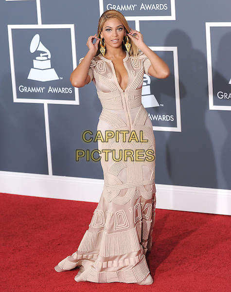 BEYONCE KNOWLES .Arrivals at the 52nd Annual GRAMMY Awards held at The Staples Center in Los Angeles, California, USA..January 31st, 2010.full length beige cream white gold dress hands pattern print low cut neckline cleavage grammys zip zipper maxi.CAP/RKE/DVS.©DVS/RockinExposures/Capital Pictures
