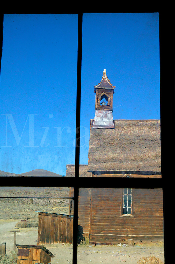 The old Methodist Church as viewed through the window of the Miller House, in the historic ghost town of Bodie.  Bodie was once a bustling gold mining town, Bodie State Historic Park, California.