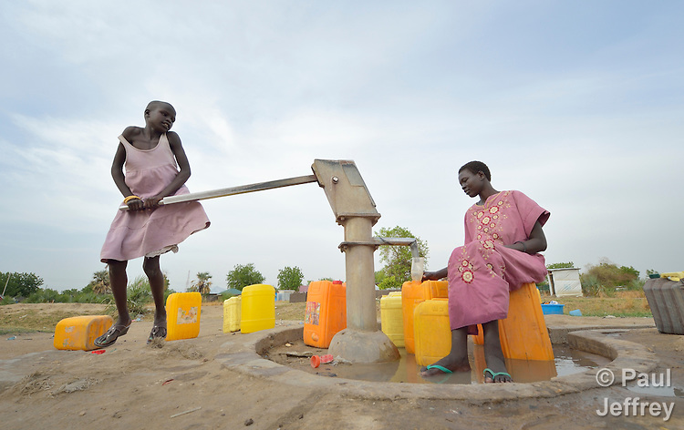 A girl pumps water with her mother in Bor, a city in South Sudan's Jonglei State that has been the scene of fierce fighting in recent months between the country's military and anti-government rebels. After fighting broke out in mid December 2013, control of the town changed hands four times in a few weeks. This well is one of dozens in the community which have been rehabilitated by Norwegian Church Aid, a member of the ACT Alliance.