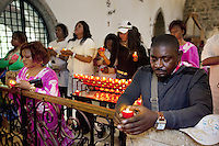 Switzerland. Canton Valais. St-Maurice. Africa Saints Pilgrimage (P&egrave;lerinage aux Saints d'Afrique). Religious <br /> ceremony in St-Maurice's abbey. African women and men pray and light candles before a catholic mass. 2.06.13 &copy; 2013 Didier Ruef