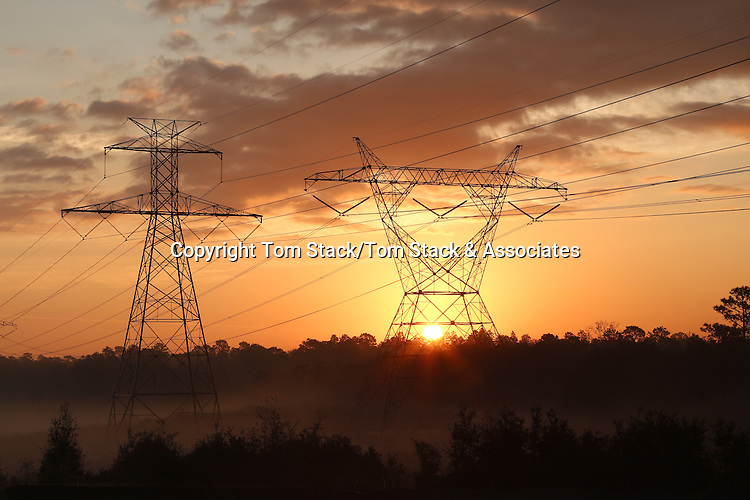 the sun rising behind a pair of towering electricity pylons