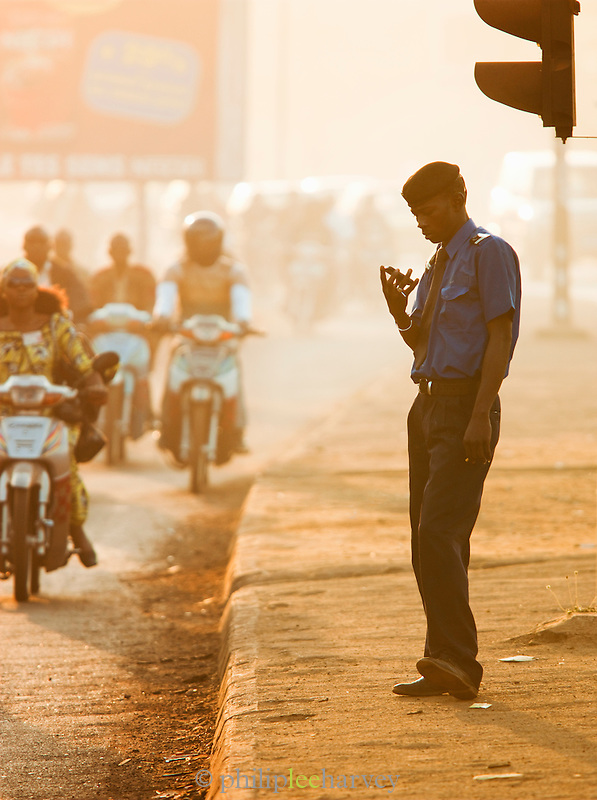 A traffic policeman checks his mobile phone, while thousands of people ride in the mornings on their mopeds, a time called Moped Mania, in Bamako, Mali
