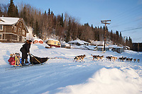 Aaron Burmeister runs up the bank of the Yukon River to Anvik during Iditarod 2009
