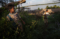 November 5, 2014 - Preah Rumkel, Stung Treng (Cambodia). Phuon Dan (15) walks with his uncle Em San (52) to the boat docked in the stretch of Mekong in front of his house.