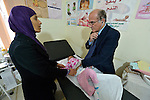 Dr. Husein Mady examines a Syrian refugee child in a clinic in Kamd El Loz, in Lebanon's Bekaa Valley. Run by the Amel Association, the clinic's work with refugees is supported by International Orthodox Christian Charities, a member of the ACT Alliance. The girl's mother observes..
