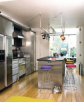 A stainless steel kitchen with folding doors, which open to a dining area. The flooring is an oak plank floor with a bevelled edge.