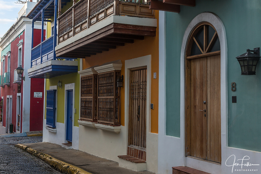Colorfully painted houses on a narrow cobblestone street in the historic colonial city of Old San Juan, Puerto Rico.