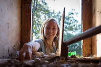 Skye Harnsberger '17, VP of Club Affairs, collects eggs from one of the two chicken coops.<br />