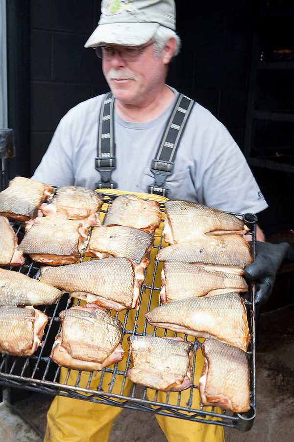 An employee in the smokehouse smokes freshly caught whitefish at Carlson's, a 5th generation fishing company in the Leland Historic District (Fishtown), Leland, Michigan, USA