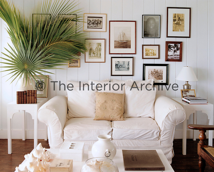 A comfortable sofa in the living room is flanked by two matching side tables and the wall above is covered in a display of framed vintage photographs