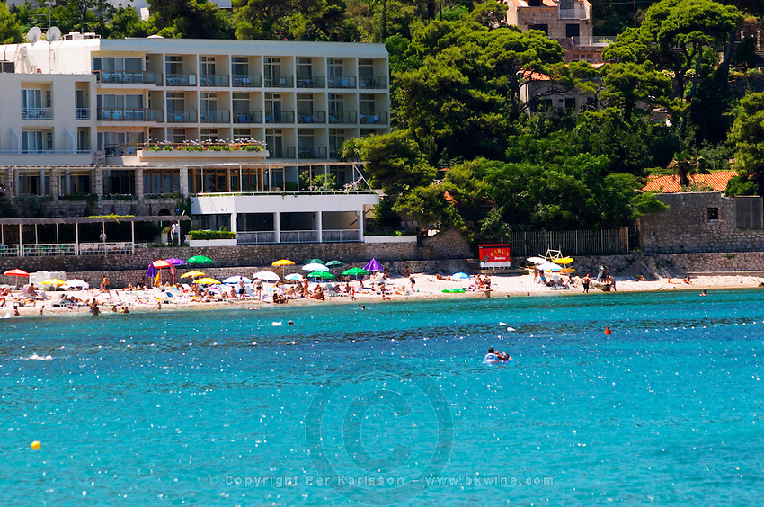 Hotel, beach, tourists, deep blue sea. Hotel and restaurant Kompas. Uvala Sumartin bay between Babin Kuk and Lapad peninsulas. Dubrovnik, new city. Dalmatian Coast, Croatia, Europe.