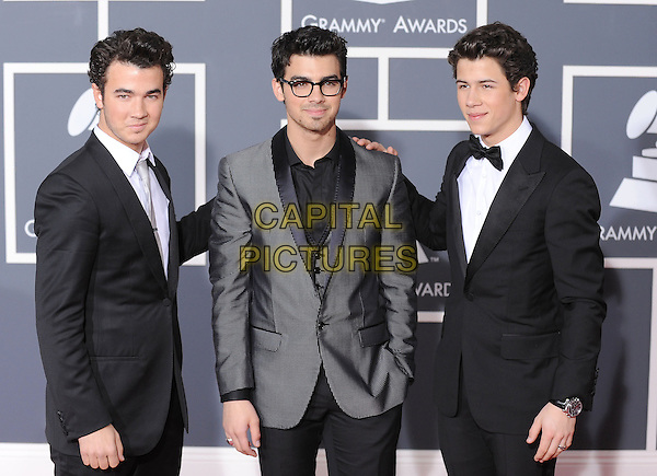KEVIN, JOE & NICK JONAS (JONAS BROTHERS) .Arrivals at the 52nd Annual GRAMMY Awards held at The Staples Center in Los Angeles, California, USA..January 31st, 2010.grammys half length black suit jacket grey gray glasses tuxedo .CAP/RKE/DVS.©DVS/RockinExposures/Capital Pictures