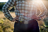 USA, Oregon, Willamette Valley, Clare Carver wears a pig belt buckle in afternoon light at her farm, Big Table Farms Winery, Gaston