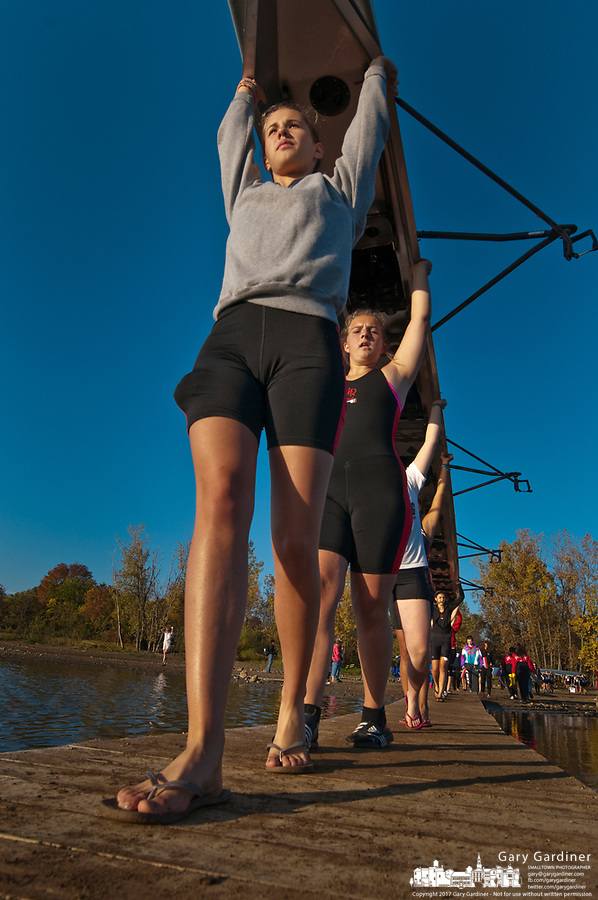 A womens rowing crew carries their boat to the water during early morning competition at the Fall Classic on Hoover Reservoir. The annual rowing competition is sponsored by the Westerville Rowing Club.
