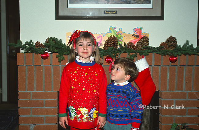Boy and girl in front onf fireplace with Christmas stockings hung