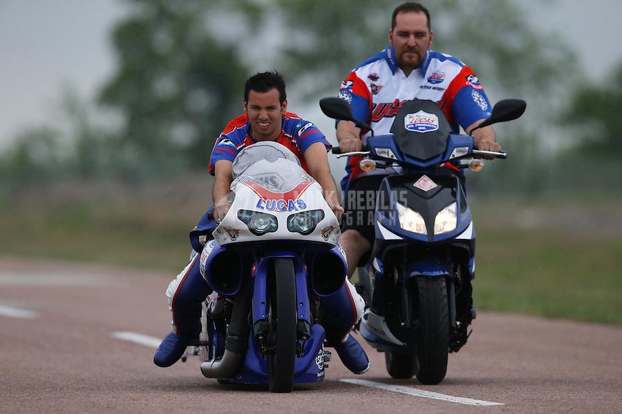 Apr. 27, 2013; Baytown, TX, USA: A crew member pushes NHRA pro stock motorcycle rider Hector Arana Jr (left) during qualifying for the Spring Nationals at Royal Purple Raceway. Mandatory Credit: Mark J. Rebilas-