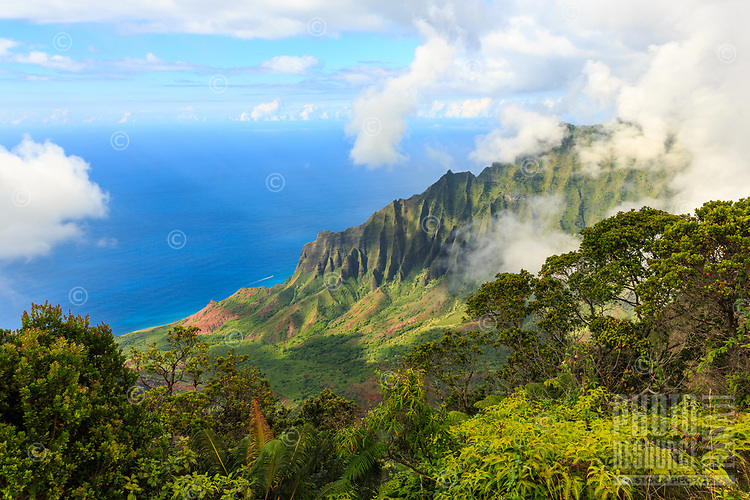 A sky of clouds lift, revealing the brilliant blue Pacific Ocean and the verdant cliffs and lush plant life of the Kalalau Valley in perfect afternoon light, Kaua'i.