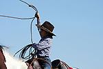 A young cowboy throwing a rope from horseback on a ranch in Texas