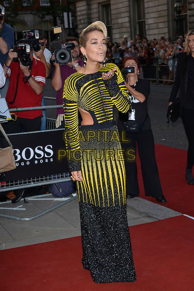Rita Ora<br /> GQ Men of the Year Awards 2013 at the Royal Opera House, London, England.<br /> September 3rd, 2013<br /> full length yellow black dress cut out away sides stripe long sleeves mouth open hand arm blowing kiss<br /> CAP/PL<br /> &copy;Phil Loftus/Capital Pictures