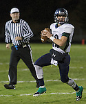 Damonte Ranch Mustangs quarterback Cade McNamara rolls out against Galena Grizzlies as referee James Hansen watches during their football game played on Thursday night, October 29, 2015 in Reno, Nevada.