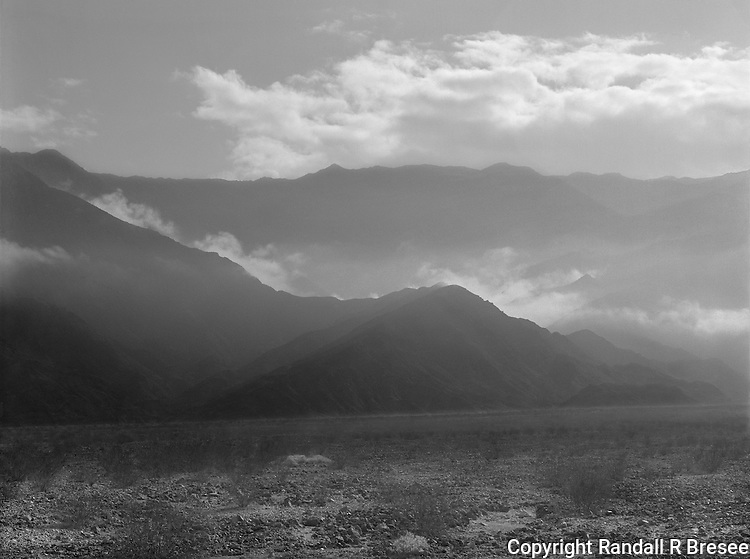 &quot;Low Clouds in Death Valley&quot; <br /> Death Valley National Park, California<br /> <br /> The most dominant feature of Death Valley National Park for me is the tremendous amount of sunlight that floods the valley floor. The photo shown here was an attempt to convey this feature where the surrounding foothills touch the valley floor.