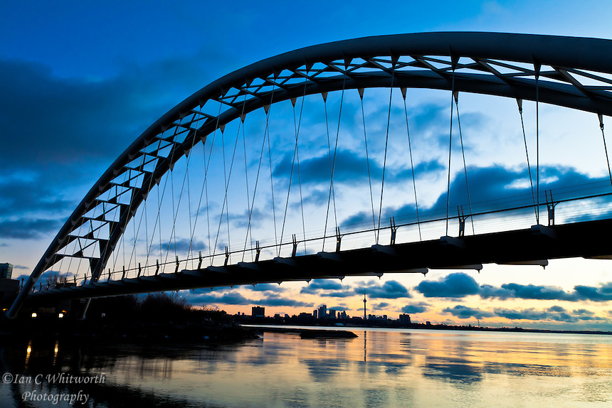 Looking under the Humber Bay Arch Bridge at dawn at the Toronto skyline.