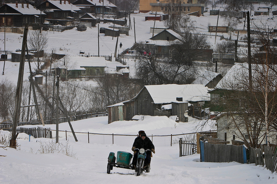 Malishevo, Russia, 29/02/2004.&amp;#xD;Two men on a motorcycle make their way uphill with the village centre behind.&amp;#xD;<br />