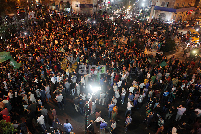 """Palestinians chant slogans during a rally to celebrate after hearing the news of the kidnapping of an Israeli soldier in Gaza strip,  in the West Bank city of Ramallah, on July 20, 2014. The Hamas' armed wing said it has captured an Israeli soldier during fighting in the Gaza Strip. Speaking on a Hamas television station, spokesman Abu Ubaida said """"we have captured a Zionist soldier and the occupation has not admitted that."""" The claim could not immediately be verified and the Israeli military said it was investigating the report. Photo by Shadi Hatem"""