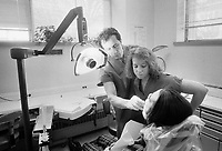 Dr. Michael Glick (left) shows a student the teeth he will be working on in a patients mouth in 1989 at the Infectious Disease Clinic at Temple University in Philadelphia, Pennsylvania. The Infectious Disease Clinic at Temple University, was established in 1988 by Dr. Glick to treat people with HIV from throughout the region. (Photo by William Thomas Cain/Cain Images)