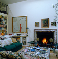 Sofas surround a large book-covered ottoman in front of a roaring fire in the living area