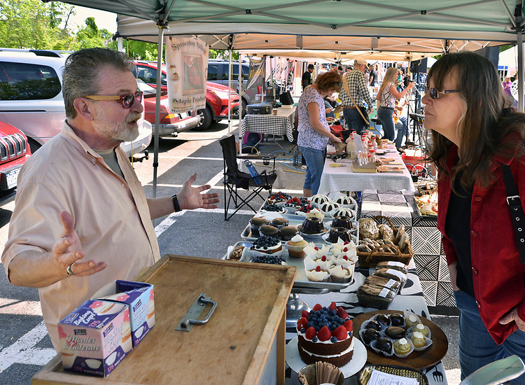 Bruce Coyle, owner of Sunporch Baked Goods, chats with customer, Ginny Christensen, of Saugerteis, at his booth at the Opening Day of the 2017 Saugerties Farmer's Market on Saturday, May 27, 2017. Photo by Jim Peppler. Copyright/Jim Peppler-2017.