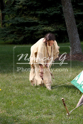 Native American Lakota Indian woman removing the tent stakes from a tipi