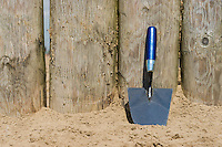 a trowel is resting against some wooden poles on a beach
