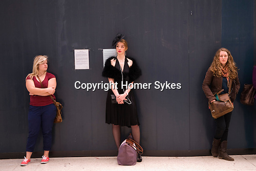 Waterloo Train Station London. Woman listening to I pod, waiting to board a train for Royal Ascot horse racing Berkshire. 2012