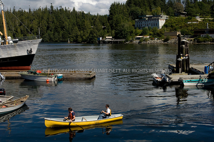 8/11/2007--Bamfield, British Columbia, Canada  .The heart of Bamfield is a collection of old fisherman's homes and piers, with a broadwalk that allows visitors to stroll along the waterfront. Kayaks, canoes and small motorboats are the main form of transportation across the inlet. .Bamfield, British Columbia, on Canada's Pacific Northwest coast on Vancouver Island, was a key station on the fragile line of telegraph cables that kept London talking to its farthest-flung imperial outposts around the world. The less pretty of the two cable buildings still stands (seen here in the background), a three-story concrete structure built for communications security..Today, Bamfield remains as a cluster of charming wooden fishermen?s houses and a few bed and breakfasts for the adventurous traveler, around a bay formed by two tiny peninsulas of cliffs that protect the village from fierce winter storms. Originally settled by the Huu-ay-aht First Nation, sits quietly south of the the more popular and booming tourist towns of Tofino and Ucluelet.©2007 Stuart Isett. All rights reserved