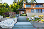 Steps lead past terraced garden beds and water feature to the front door of this contemporary home.