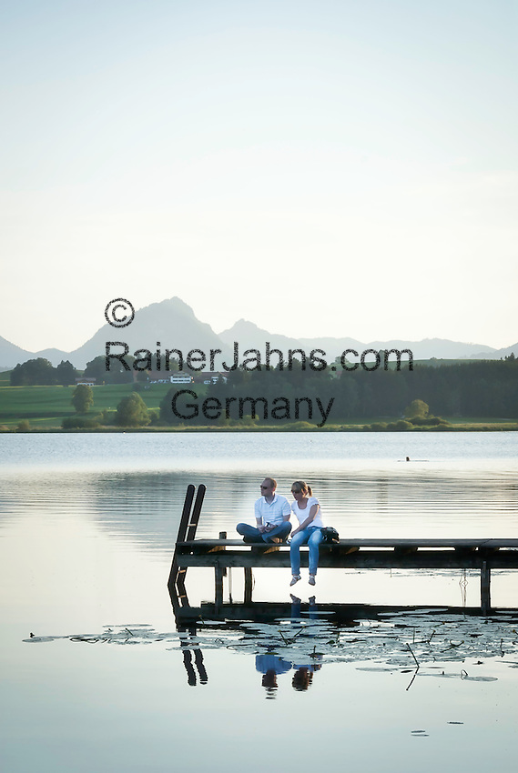 Germany, Bavaria, Upper Swabia, East-Allgaeu, Hopfen at Hopfen Lake: couple sitting on bathing jetty, at background the Allgaeu Alps | Deutschland, Bayern, Oberschwaben, Ost-Allgaeu, Hopfen am See: Paerchen sitzt auf einem Badesteg, vertieft in eine Unterhaltung, im Hintergrund die Allgaeuer Alpen