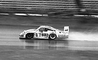 The #6 Porsche of A. j> Foyt Jr., Bob Wollek, Claude Ballot-Lena and Preston Henn kicks up a rooster tail as it races to victory in the rain during the 1983 24 Hours of Daytona , Daytona Internationa Speedway, Daytona Beach, FL, February 1-2, 1983.  (Photo by Brian Cleary / www.bcpix.com)
