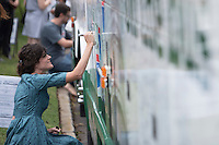 NWA Democrat-Gazette/J.T. WAMPLER Kerri Packwood of Fayetteville signs the bus Sunday Sept. 13, 2015 during the fourth national &ldquo;Nuns on the Bus&rdquo; tour at St. Paul&rsquo;s Episcopal Church in Fayetteville. <br /> <br /> ((SEE 001 PHOTO FOR EXTENDED CUTLINE INFO))