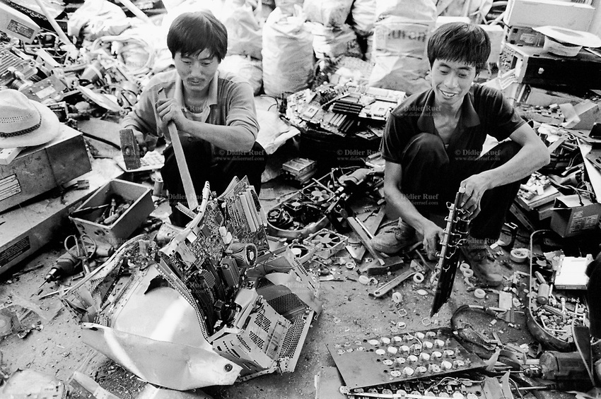 China. Province of Guangdong. The village of Nanyang is part of the town of Guiyu. Workers take down by hand old and discarded computers and electronic components which will be laid on the ground. The various parts will be recycled for its metals, electric cables, terminals, printed and integrated circuits, chips,... © 2004 Didier Ruef