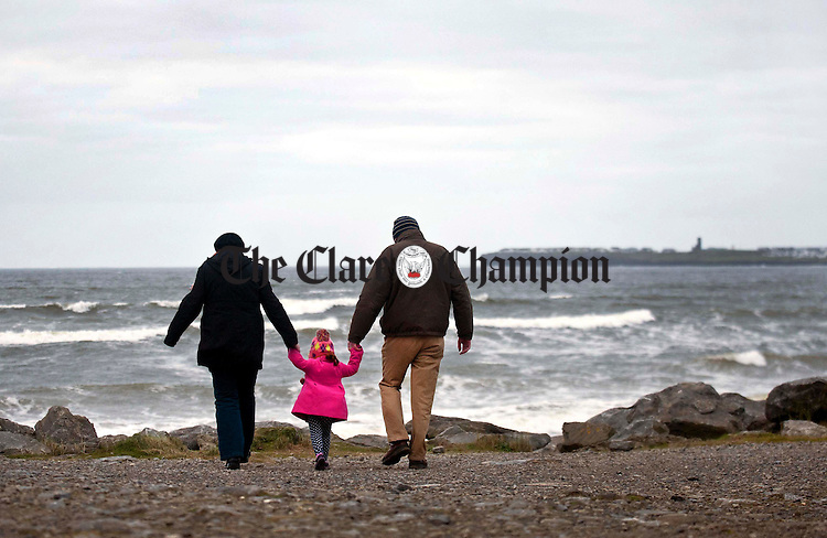Chloe Sugrue from Liscannor enjoying a New Year's stroll with her parents, Tracey and Liam, at Lahinch Strand. Photograph by Declan Monaghan