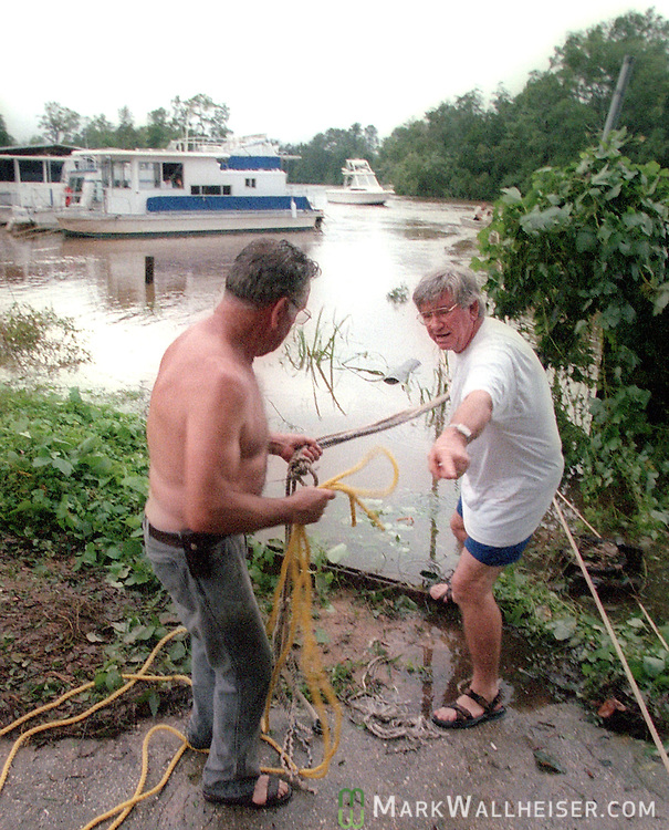 Neighbors help secure boats that have broken loose in the flooded Blackwater River near Milton, Florida after Hurricane Georges September 29, 1998.  Georges made six landfalls through the Caribbean Sea and Gulf of Mexico before making it's 7th and final landfall near Biloxi.  604 people were killed mostly in Dominican Republic and haiti.  Because of the extensive damage, the name Georges was retired and will never be used again.