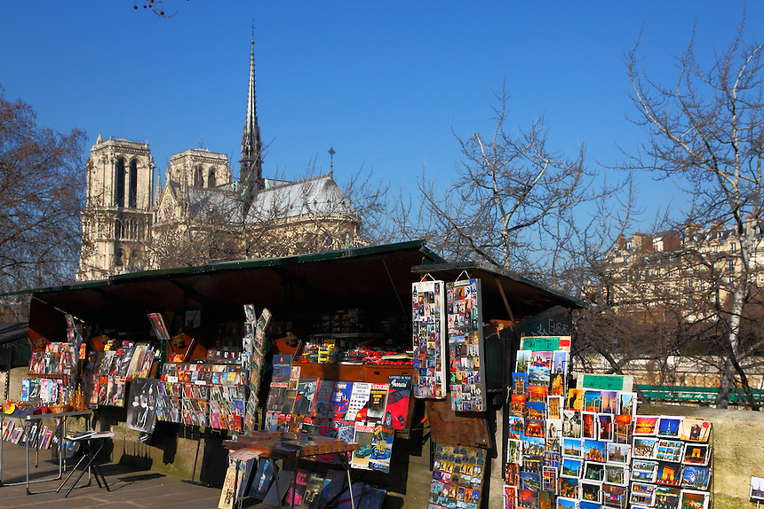 Paris Left Bank: Along the Seine river, the typical stand of a bookseller (bouquiniste) on the background of Notre Dame.<br />