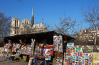 Along the Seine river in Paris, the typical stand of a bookseller (bouquiniste) on the background of the Notre Dame church. Digitally Improved Photo.