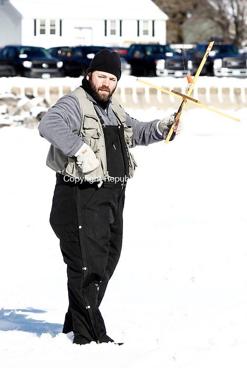 Winsted, CT- 25 January 2015-012515CM05- Michael Pierce of Colebrook checks his fishing rig during the third annual Northwest Sporting Goods Ice Fishing Derby  at Highland Lake in Winsted on Sunday. The event was held as  a fundraiser for the American Legion Post 43's national emergency fund, and local veterans and their children.  Christopher Massa Republican-American