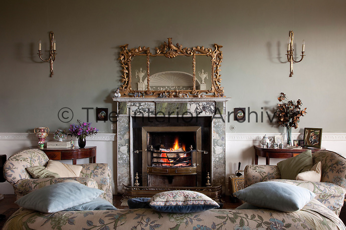 An ornate gilded mirror decorates the marble fireplace in the drawing room, surrounded by cosy armchairs and scatter cushions