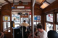 Inside a typical streetcar (trolley) going down  a narrow streetl, Lisbon, Portugal. Although Lisbon has a modern fleet of trams, climbing the steep hills and narrow streets of Lisbon is mostly done in small streetcars, that remain faithful to their style since their first uses in the city, including even the wooden benches and driving system inside. Shown is the world famous line 28, selected by National Geographic as one of the top 10 trolley rides in the world.