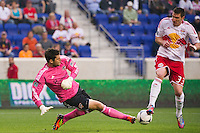 Kenny Cooper (33) of the New York Red Bulls deflects a clearance by Houston Dynamo goalkeeper Tally Hall (1) in for a goal during the first half of a Major League Soccer (MLS) match at Red Bull Arena in Harrison, NJ, on May 09, 2012.
