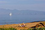 A young couple enjoy the sun on Kaanapali beach on the island of Maui.